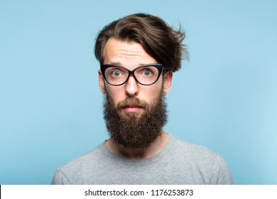 worried nervous alarmed bearded hipster guy wearing cat eye glasses. stylish modern fashionist. portrait of a geeky quirky eccentric man on blue background.