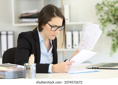 Worried office worker reading sales reports sitting in a desktop at workplace