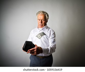 Worried old man in white is looking at an empty wallet. Dollar, heavy expenses, taxes and accounting concept.