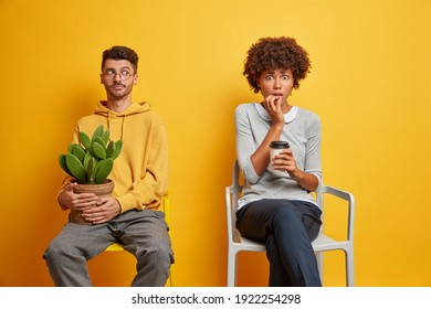 Worried puzzled young Afro American woman drinks coffee looks nervous at camera drinks takeaway coffee poses on comfortable chair indoor serious thoughtful guy poses near with potted cactus.