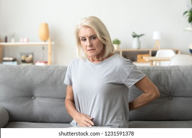 Worried sad mature older woman touching back feeling ache massaging tensed muscles, upset senior female suffering from chronic lower lumbar pain, backache arthritis osteoarthritis radiculitis concept