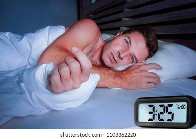 worried sad young attractive man awake lying sleepless on bed with eyes wide opened suffering insomnia sleeping disorder depressed and thoughtful with alarm clock pointing late night hour