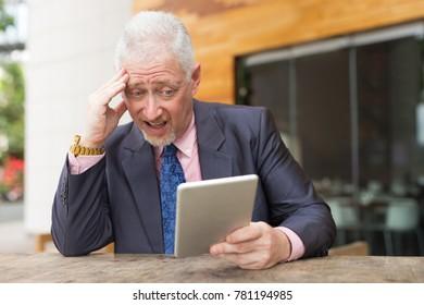 Worried Senior Business Leader Using Tablet