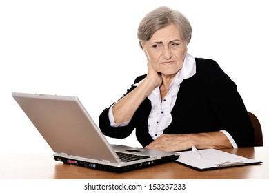Worried senior businesswoman working on laptop against white background