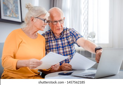 Worried senior couple checking bills using laptop at home
