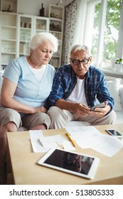 Worried senior couple checking the bills at home