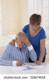 Worried Senior Couple Checking Finances And Going Through Bills