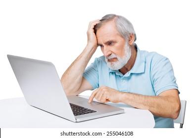 Worried senior man using laptop