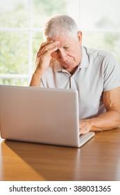 Worried senior man using laptop at home
