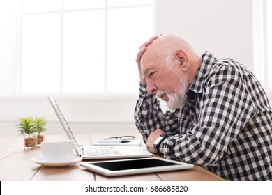 Worried senior man using laptop at home. Sad mature male have problems with using internet, copy space
