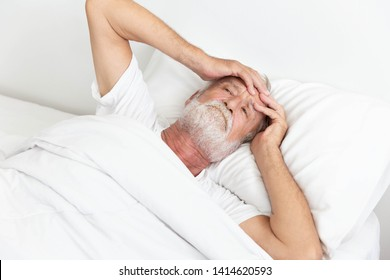 Worried senior retirement man lying awake in his bed