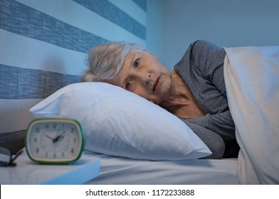 Worried senior woman in bed at night suffering from insomnia. Old woman lying in bed with open eyes. Mature woman unable to sleep at home.