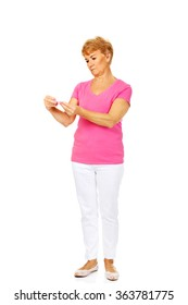 Worried senior woman holding thermometer