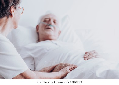 Worried senior woman taking care of a dying man at hospital