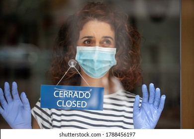 Worried shop assistant closing her retail business to the public during the pandemic quarantine covid 19 in Spain. Economical Financial crisis and coronavirus concept.