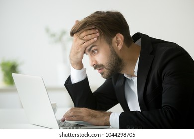 Worried stressed businessman in suit shocked by bad news using laptop at work, desperate bankrupt investor lost money online depressed by financial problem debt, frustrated worker tired of overwork