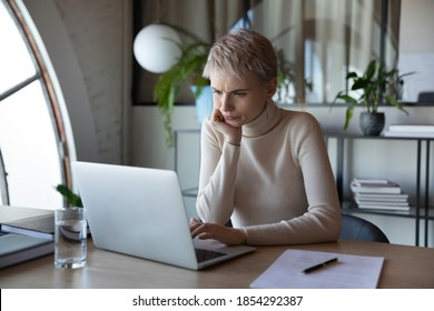 Worried stressed businesswoman looking at laptop screen, doubting, reading bad news in email, sitting at work desk in office, upset serious female employee working on difficult project