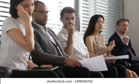 Worried stressed mixed race people applicants candidates sitting at office in row line queue on chairs, holding resume or documents, waiting for high paid dream job interview with hr manager or boss.