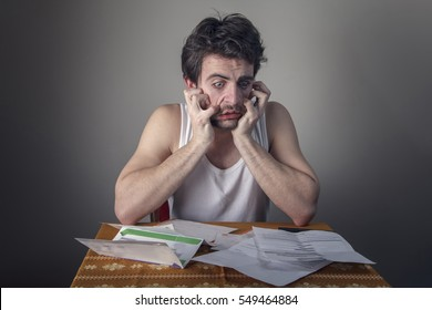 Worried, stressed out and depressed young man crying over the bills he has to pay