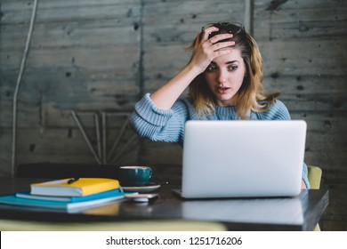 Worried stressed woman forgot about important think during remote work at laptop computer in cafe interior.Hipster girl done stupid mistake during freelance deadline on netbook sitting at table