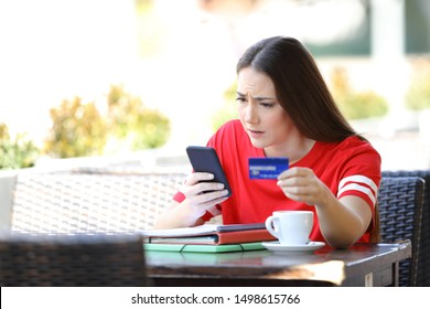 Worried student paying online with credit card sitting in a coffee shop terrace