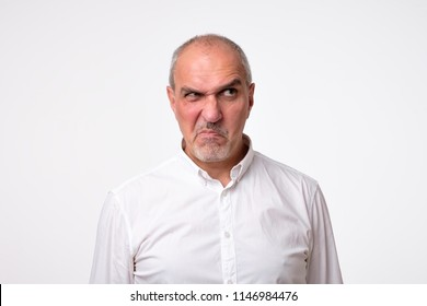 worried suspicious mature hispanic man isolated against white studio background. His face is in disgust grimace. He is looking aside