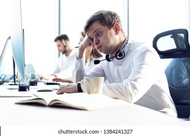 Worried or tired business man with headset working on computer in office