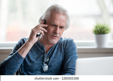 Worried unsatisfied middle aged male sitting at home make business call solve issues distantly communicating use gadget. Customer having difficulties telling about laptop problems to service support