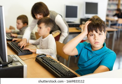 Worried upset boy sitting in computer class of school library on background with working classmates and teacher