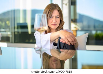 Worried withdrawn woman sitting staring at a glass of wine thinking deeply with a sombre expression outdoors at a table on her patio with reflection on the table