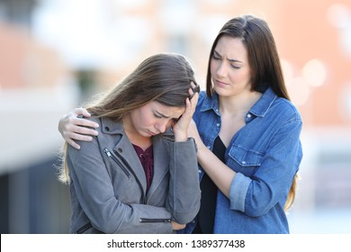 Worried woman comforting her sad friend who is complaining in the street