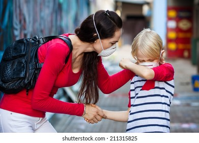 A worried woman is helping her sick son who is coughing. Both are wearing protective face masks for pollution or virus.