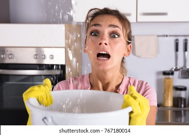 Worried Woman Holding A Bucket While Water Droplets Leak From Ceiling In Kitchen At Home
