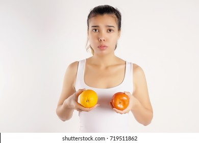 Worried Woman Holding Two Difference Colour of Oranges in front of Her Breast, Breast Cancer Awareness Concept