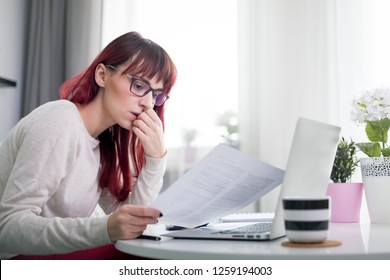 Worried woman at home checking financial documents using calculator and laptop