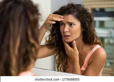 Worried woman is looking her first wrinkles in the bathroom.