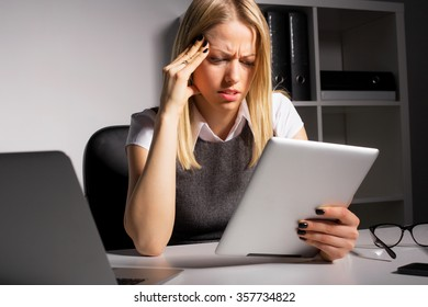 Worried woman looking at tablet