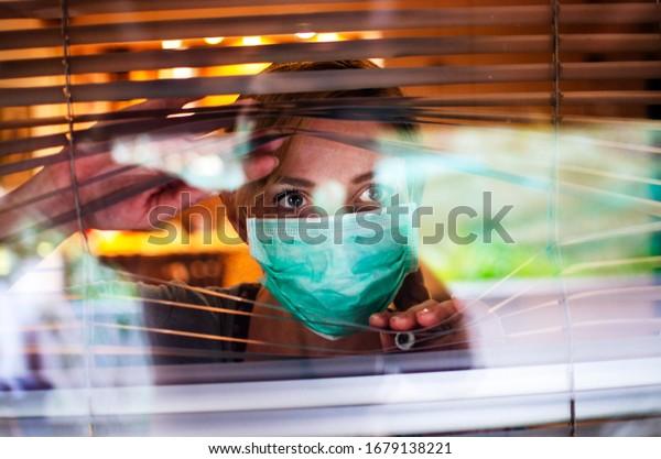 Mujer preocupada mirando a través de la ventana desde casa en cuarentena durante el virus Corona. Mujer ansiosa en aislamiento de auto distanciamiento debido a Covid-19. Permanezca en casa en tiempo de concepto pandémico.