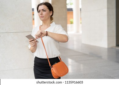 Worried woman looking at watch and running to work. Portrait of mid adult Caucasian businesswoman with smartphone in hurry for meeting. Being late concept