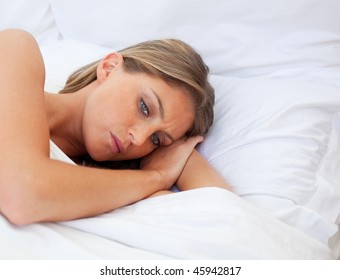 Worried woman lying on her bed after having a row with her husband