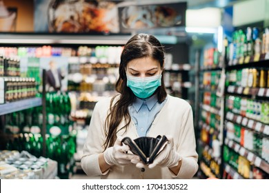 Worried woman with mask groceries shopping in supermarket looking at empty wallet.Not enough money to buy food.Covid-19 quarantine lockdown.Financial problems anxiety.Unemployed person in money crisis