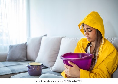 Worried Woman in Raincoat Holding Bucket While Water Droplets Leak From Ceiling in Living Room. Woman Holding Bucket While Water Droplets Leak From Ceiling. Roof Leaking