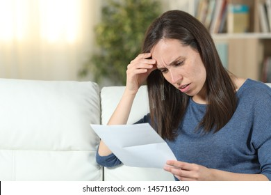 Worried woman reading a letter sitting on a couch in the living room at home