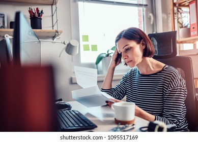 Worried woman sitting by the window reading mail in the office