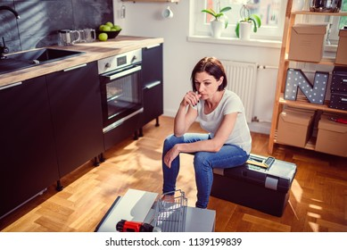 Worried woman sitting on a toolbox during renovating kitchen