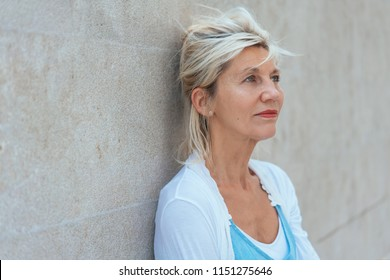 Worried woman standing thinking leaning on a wall staring ahead with a serious expression deep in thought