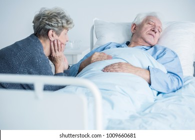 Worried woman taking care of her sick husband during a visit in the hospital