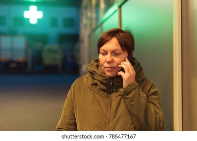 Worried woman talking on mobile phone in front of drugstore at night. Adult female using telephone to consult with doctor before buying medication in pharmacy store. Violet toned shadows.