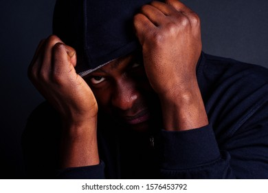 worried young african american mele wearing gray hat and black hoody with hood hiding from the rapist s blow attacker studio black dackground