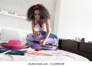 Worried young black woman packing bags for holiday. Girl trying to close full suitcase for vacation, getting ready for traveling